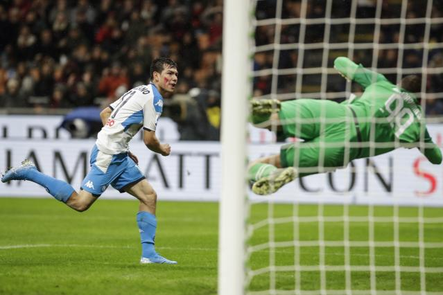 Napoli's Hirving Lozano scores past AC Milan goalkeeper Gianluigi Donnarumma during the Serie A soccer match between AC Milan and Napoli, at the San Siro stadium in Milan, Italy, Saturday, Nov. 23, 2019. (AP Photo/Luca Bruno)