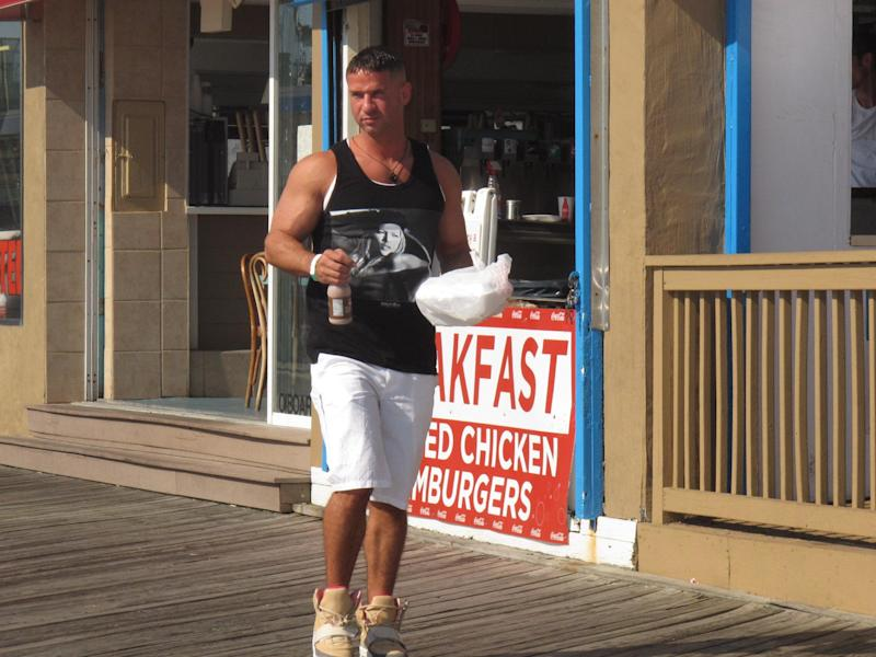 "This July 3, 2012 photo shows ""Jersey Shore"" cast member Mike ""The Situation"" Sorrentino carrying breakfast out of a restaurant on the Seaside Heights, N.J. boardwalk as filming of the the MTV series was winding down its sixth season. The network says the cast wrapped up filming with a group hug at the end of the July 4th holiday weekend. Sorrentino, Nicole ""Snooki"" Polizzi, Jenny ""JWoww"" Farley, Deena Nicole Cortese, Vinny Guadagnino, Paul ""Pauly D"" DelVecchio, Samantha Giancola and Ronnie Ortiz-Magro then loaded their luggage and drove off. MTV says Season 6 will feature Cortese's arrest after she was dancing in the streets. She pleaded guilty to failing to use the sidewalk. (AP Photo/Wayne Parry)"