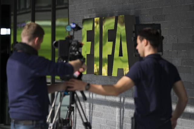 A TV crew prepares to film in front of the FIFA logo at the FIFA headquarters on September 25, 2015 in Zurich (AFP Photo/Fabrice Coffrini)