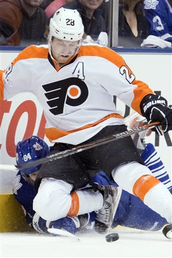 Toronto Maple Leafs' Mikhail Grabovski (28) battles for the puck with Philadelphia Flyers' Claude Giroux (84) during the first period of an NHL hockey game in Toronto on Saturday, March 10, 2012. (AP Photo/The Canadian Press, Chris Young)