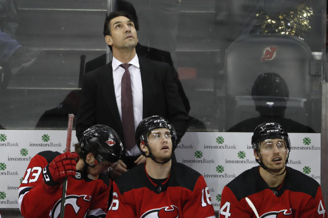 New Jersey Devils interim coach Alain Nasreddine watches a video replay of the third goal scored by Vegas Golden Knights center Jonathan Marchessault during the third period of an NHL hockey game, Tuesday, Dec. 3, 2019, in Newark, N.J. The Golden Knights defeated the Devils 4-3 in Nasreddine's first game in place of fired head coach John Hynes. (AP Photo/Kathy Willens)