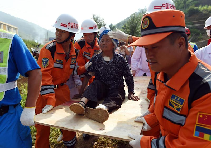 Rescue personnel carry an injured elderly earthquake survivor on a plank of wood, to a helicopter in Longtoushan, China's southwest Yunnan province, on August 6, 2014 (AFP Photo/Greg Barker)