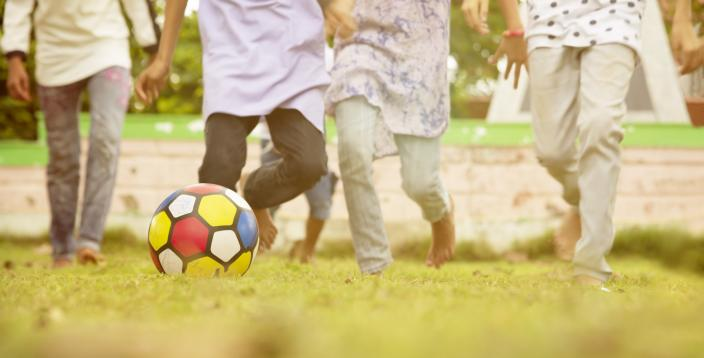 Selective focus on football, Group of kids running and playing football at park - Concept showing of children playing outdoor games during vacation