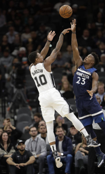 San Antonio Spurs guard DeMar DeRozan (10) shoots over Minnesota Timberwolves guard Jimmy Butler (23) during the first half of an NBA basketball game, Wednesday, Oct. 17, 2018, in San Antonio. (AP Photo/Eric Gay)