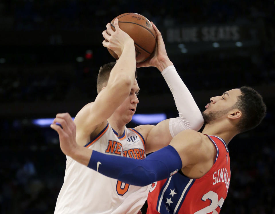 New York Knicks' Kristaps Porzingis tries to move past Philadelphia 76ers' Ben Simmons during the first half of the NBA basketball game, Monday, Dec. 25, 2017, in New York. (AP Photo/Seth Wenig)