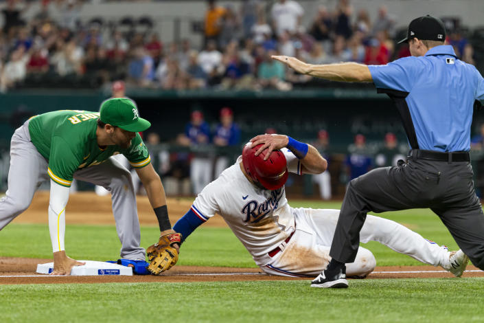 Texas Rangers' Joey Gallo, center, avoids the tag of Oakland Athletics third baseman Chad Pinder, left, to safely take third base during the first inning of a baseball game, Monday, June 21, 2021, in Arlington, Texas. (AP Photo/Sam Hodde)