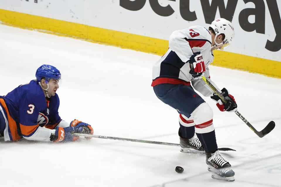 New York Islanders defenseman Adam Pelech (3) tries to prevent Washington Capitals left wing Conor Sheary (73) from getting to the puck during the second period of an NHL hockey game Thursday, April 22, 2021, in Uniondale, N.Y. (AP Photo/Kathy Willens)