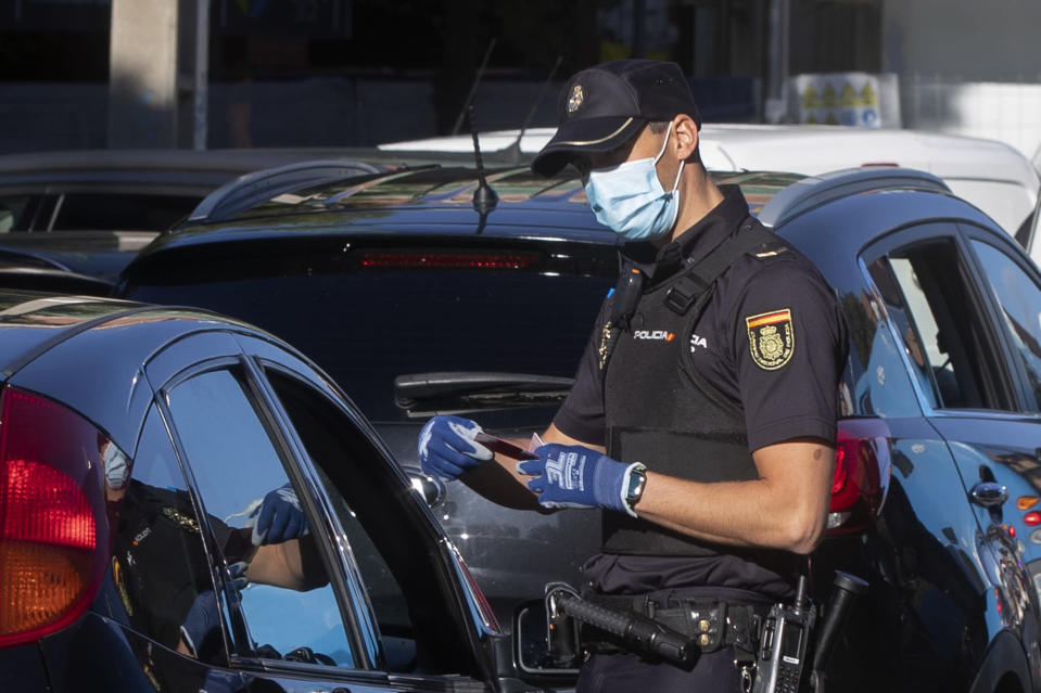 A police officer checks a driver's documents at a checkpoint on the outskirts of Madrid, Spain, Saturday, Oct. 3, 2020. Madrid is on a partial lockdown complying with an order from the Spanish government due to the high COVID-19 cases but determined to fight it in the courts. Measures that ban all nonessential trips in and out of the capital and nine of its suburbs, covering around 4.8 million people. (AP Photo/Paul White)