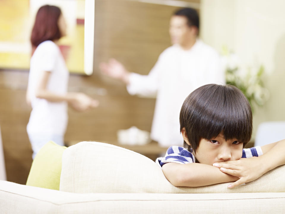 asian child appears sad and unhappy while parents quarreling in the background.