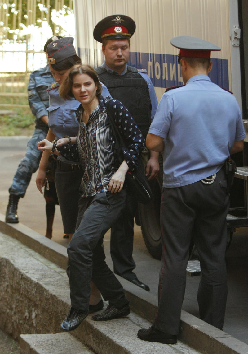 Yekaterina Samutsevich, left, a member of feminist punk group Pussy Riot is escorted to a court room in Moscow, Russia, Wednesday, Aug. 8, 2012. Prosecutors on Tuesday called for three-year prison sentences for feminist punk rockers who gave an impromptu performance in Moscow's main cathedral to call for an end to Vladimir Putin's rule, in a case that has caused international outrage and split Russian society.(AP Photo/Alexander Zemlianichenko)