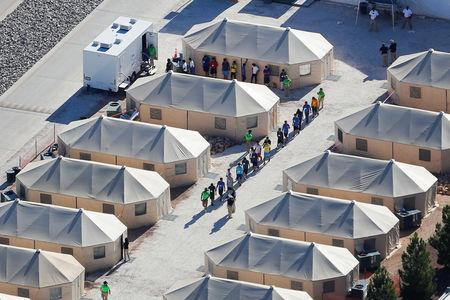 "FILE PHOTO: Immigrant children now housed in a tent encampment under the new ""zero tolerance"" policy by the Trump administration are shown walking in single file at the facility near the Mexican border in Tornillo, Texas, U.S. June 19, 2018.   REUTERS/Mike Blake"