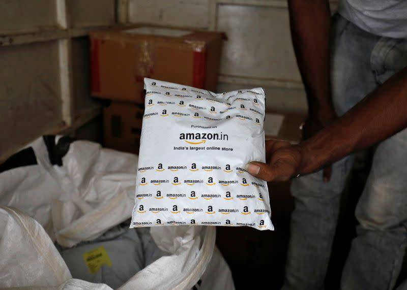 A worker sorts delivery packages in a van outside an Amazon facility in Ahmedabad