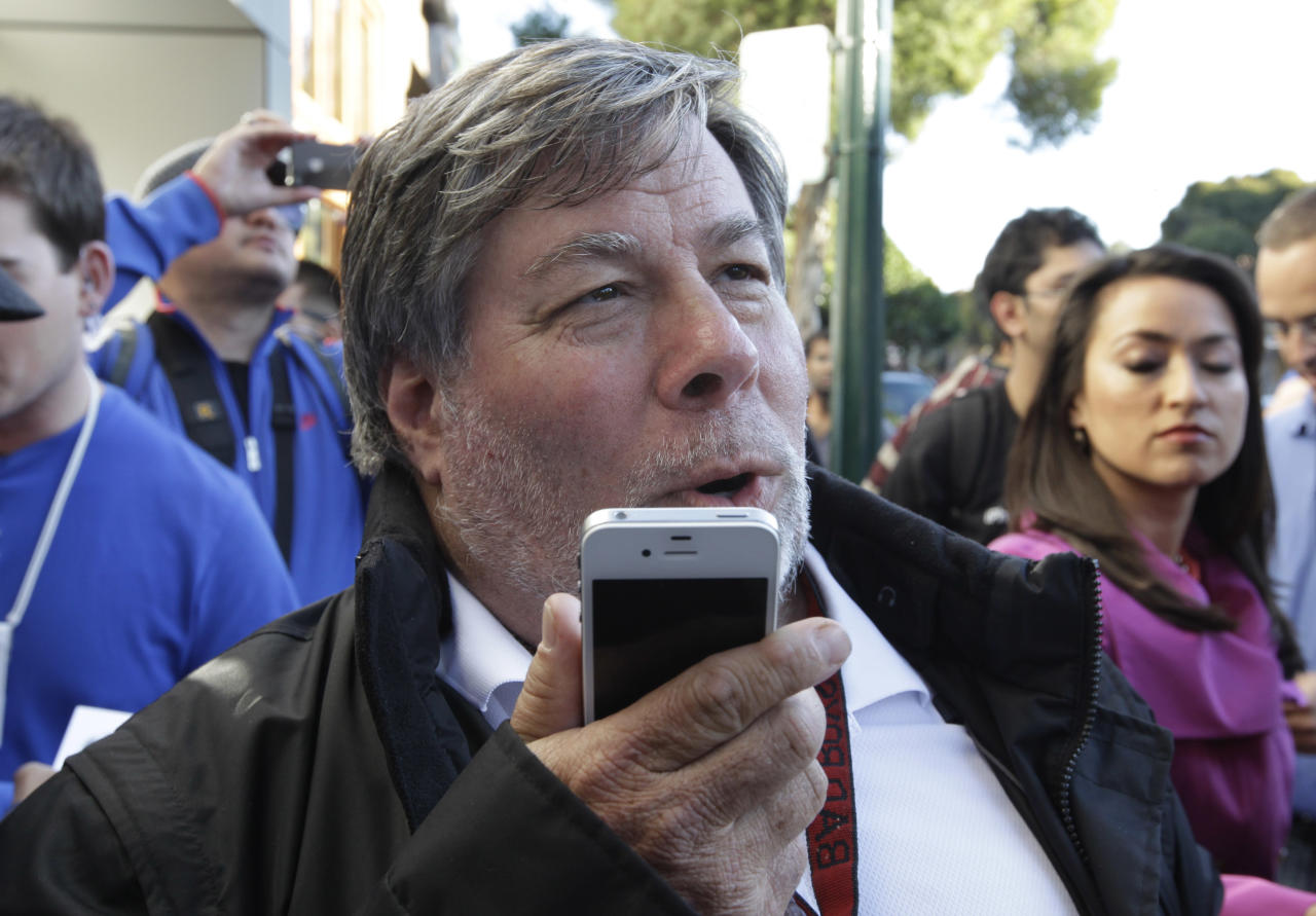 Apple co-founder Steve Wozniak uses the new voice feature on his new Apple iPhone 4S at the Apple store in Los Gatos, Calif., Friday, Oct. 14, 2011. Wozniak waited 20 hours in line to be the first Apple customer at the Los Gatos Apple store, to buy the new iPhone. (AP Photo/Paul Sakuma)