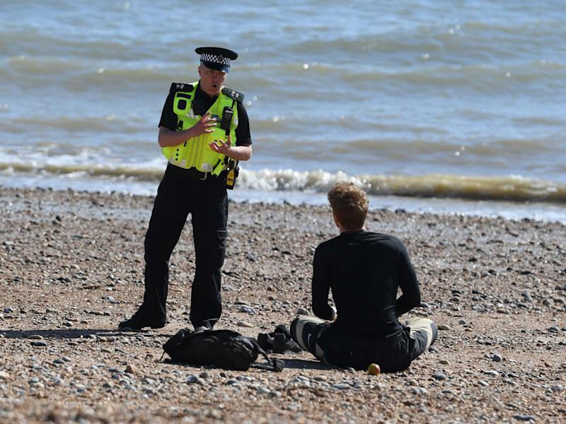 A police officer moves a member of the public off Brighton beach on April 04, 2020: Getty Images