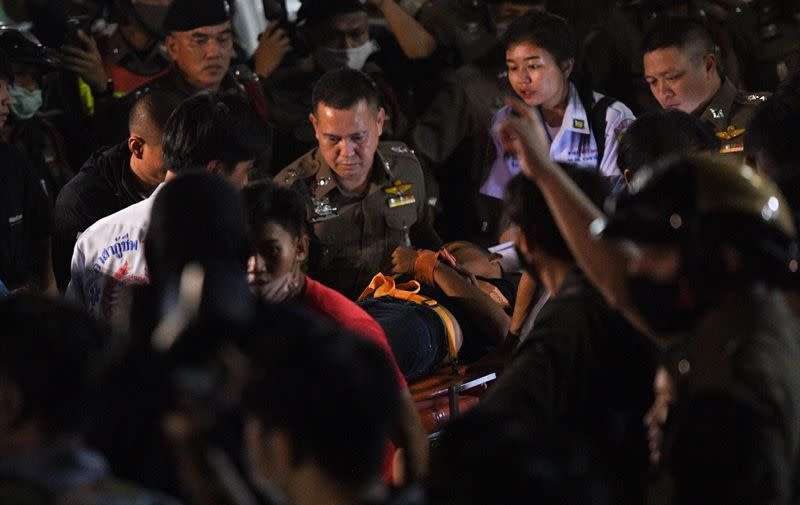 "Panupong ""Mike Rayong"" Jadnok is carried on a stretcher by police at Prachachuen police station in Bangkok"
