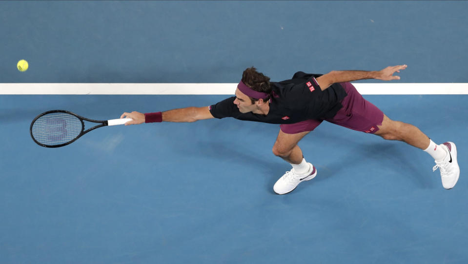 Switzerland's Roger Federer stretches out for a backhand return to Serbia's Filip Krajinovic during their second round singles match at the Australian Open tennis championship in Melbourne, Australia, Wednesday, Jan. 22, 2020. (AP Photo/Lee Jin-man)