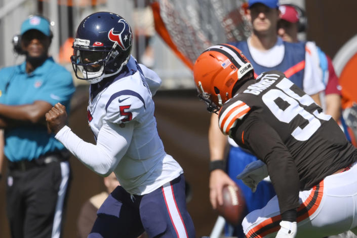 Houston Texans quarterback Tyrod Taylor (5) rushes for a 15-yard touchdown against Cleveland Browns defensive end Myles Garrett (95) during the first half of an NFL football game, Sunday, Sept. 19, 2021, in Cleveland. (AP Photo/David Richard)