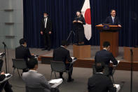 Japan's Prime Minister Yoshihide Suga, right, speaks during a press conference at the prime minister's official residence Friday, May 28, 2021, in Tokyo. Japan extended a coronavirus state of emergency in Tokyo and other areas for 20 more days on Friday, with infections still not slowing as it prepares to host the Olympics in just over 50 days. (Behrouz Mehri/Pool Photo via AP)