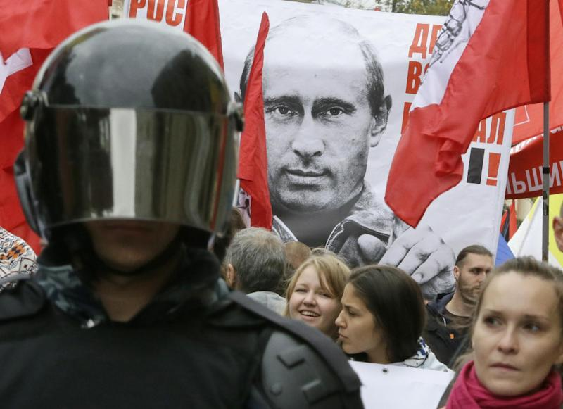 "Protesters hold a poster depicting Russia's President Vladimir Putin as they march during a protest rally in St. Petersburg, Russia, Saturday, Sept. 15, 2012. The sign reads: ""Prices, tariffs and poverty rise, you chose all this"". Thousands of protesters marched across downtown Moscow and St. Petersburg on Saturday in the first major rally in three months against President Vladimir Putin, while defying the Kremlin's ongoing efforts to crackdown on opposition. (AP Photo/Dmitry Lovetsky)"