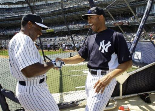 New York Yankees Rickey Henderson, left, greets Yankees relief pitcher Mariano Rivera before the Old Timers Day baseball game Sunday, June 23, 2013, in New York. (AP Photo/Kathy Willens)