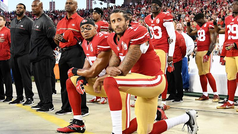Seen here Colin Kaepernick (R) kneels in protest against the American national anthem.