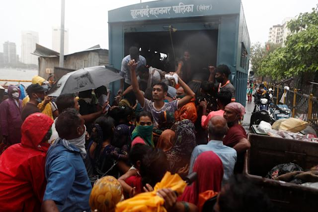 People scramble to enter a truck during an evacuation of a slum off the coast of the Arabian sea in Mumbai as cyclone Nisarga makes its landfall on the outskirts of the city on June, 3, 2020. REUTERS/Francis Mascarenhas