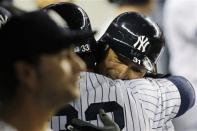 New York Yankees' Nick Swisher (33) and Ichiro Suzuki embrace in the dugout after Suzuki scored on Swisher's fourth-inning grand slam against the Toronto Blue Jays during their baseball game at Yankee Stadium in New York, Thursday, Sept. 20, 2012. The Yankees won 10-7. (AP Photo/Kathy Willens)