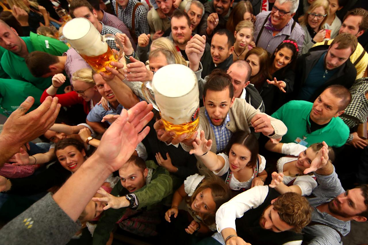 <p>Visitors reach for the first mugs of beer during the opening day of the 184th Oktoberfest in Munich. (Reuters/Michael Dalder) </p>