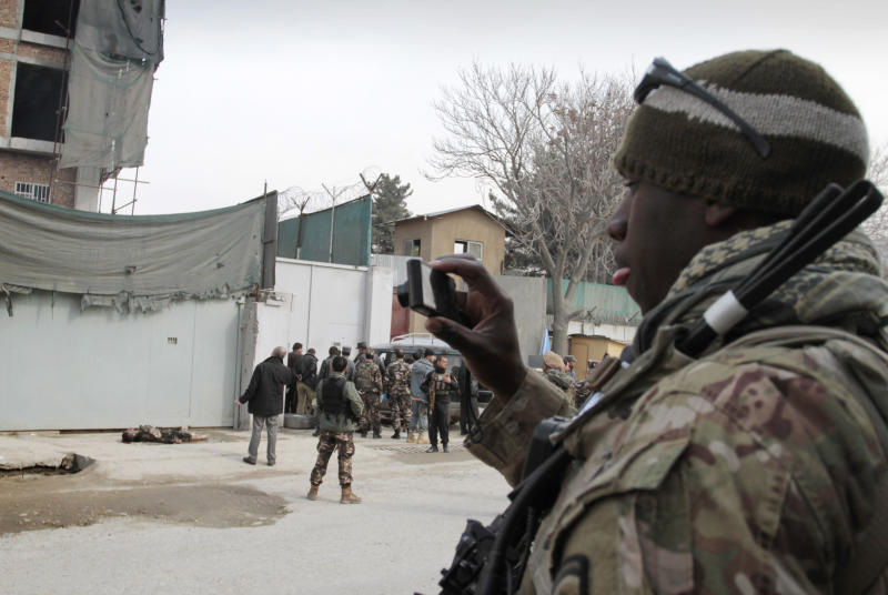 A U.S. soldier, right, photographs the scene where an insurgent was shot to death near an Afghan intelligence office in Kabul, Afghanistan, Sunday, Feb. 24, 2013. A series of early morning attacks hit eastern Afghanistan Sunday, with three separate suicide bombings in outlying provinces and a shootout between security forces and a would-be attacker in the capital city of Kabul.  (AP Photo/Musadeq Sadeq)
