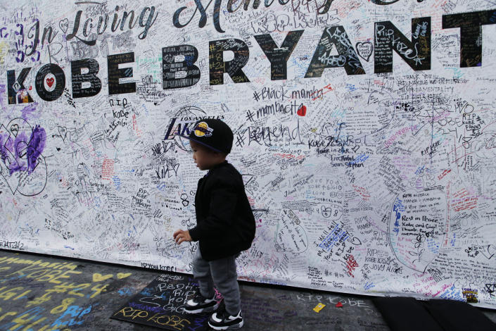 A boy walks by a standing board with messages for the late Kobe Bryant at a memorial for Bryant in front of Staples Center in Los Angeles Sunday, Feb. 2, 2020. Bryant, the 18-time NBA All-Star who won five championships and became one of the greatest basketball players of his generation during a 20-year career with the Lakers, died in a helicopter crash Sunday, Jan. 26. (AP Photo/Damian Dovarganes)