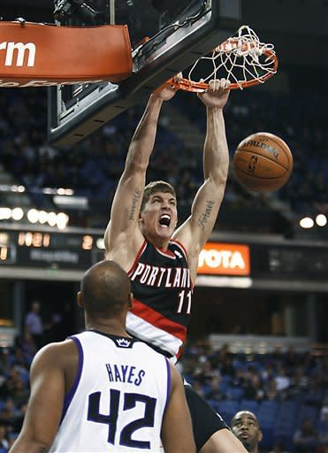 Portland Trail Blazers center Meyers Leonard (11) breaks away for a dunk over Sacramento Kings defender Chuck Hayes during the first half of an NBA basketball game in Sacramento, Calif., on Sunday, Dec. 23, 2012.(AP Photo/Steve Yeater)