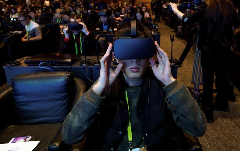 A showgoer wears an Oculus Rift vitual reality headset during the Intel press conference at CES in Las Vegas