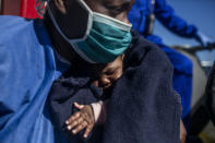 33-year old Sandrine from Cameroon holds her three months old son Moise moments before leaving the Spanish NGO Open Arms rescue vessel in the Sicilian port of Empedocle, Italy, Tuesday, Feb. 16, 2021. Various African migrants drifting in the Mediterranean Sea after fleeing Libya on unseaworthy boats have been rescued. In recent days, the Libyans had already thwarted eight rescue attempts by the Open Arms, a Spanish NGO vessel, harassing and threatening its crew in international waters. (AP Photo/Bruno Thevenin)