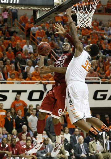Oklahoma forward Amath M'Baye (22) shoots as Oklahoma State guard Marcus Smart (33) defends in the second half of an NCAA college basketball game in Stillwater, Okla., Saturday, Feb. 16, 2013. Oklahoma State won 84-79. (AP Photo/Sue Ogrocki)