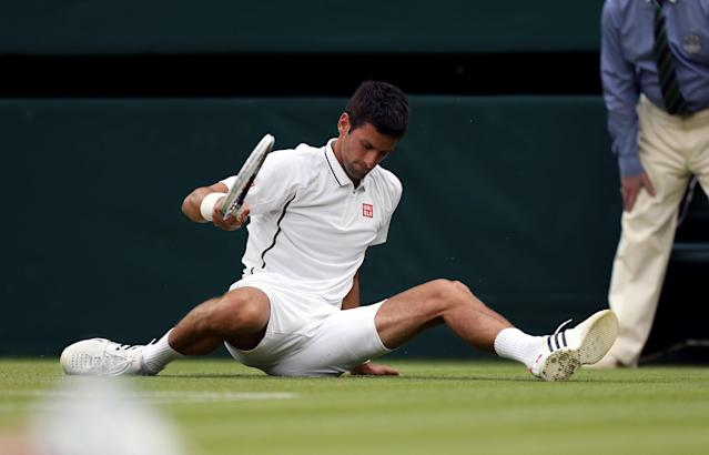 Serbia's Novak Djokovic slips over during his match against USA's Bobby Reynolds during day four of the Wimbledon Championships at The All England Lawn Tennis and Croquet Club, Wimbledon.