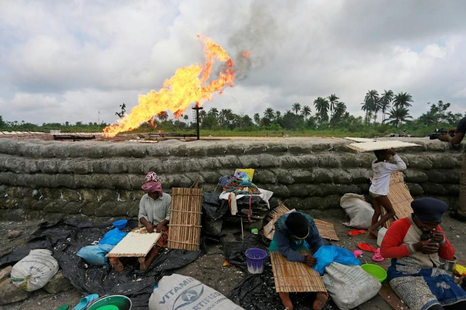 A family prepare tapioca behind sand barriers surrounding a gas flaring furnace at a flow station in Ughelli, Delta StateA family prepare tapioca, which is derived from cassava paste, behind sand barriers surrounding a gas flaring furnace at a flow station in Ughelli, Delta State, Nigeria September 17, 2020. Picture taken September 17, 2020. REUTERS/Afolabi Sotunde