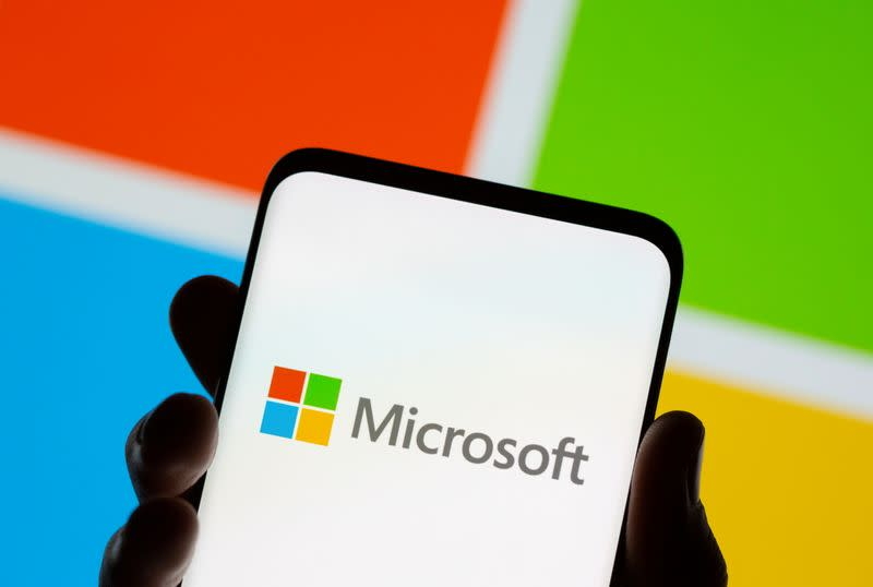 Smartphone is seen in front of Microsoft logo displayed in this illustration taken