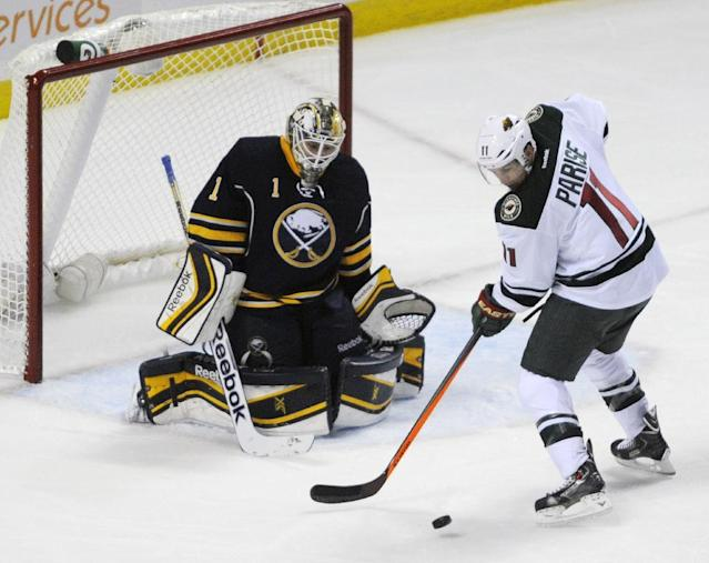 Buffalo Sabres goaltender Jhonas Enroth (1), of Sweden, watches the puck while Minnesota Wild left winger Zach Parise (11) tries to deflect the shot during the third period of an NHL hockey game in Buffalo, N.Y., Monday, Oct. 14, 2013. Minnesota won 2-1. (AP Photo/Gary Wiepert)