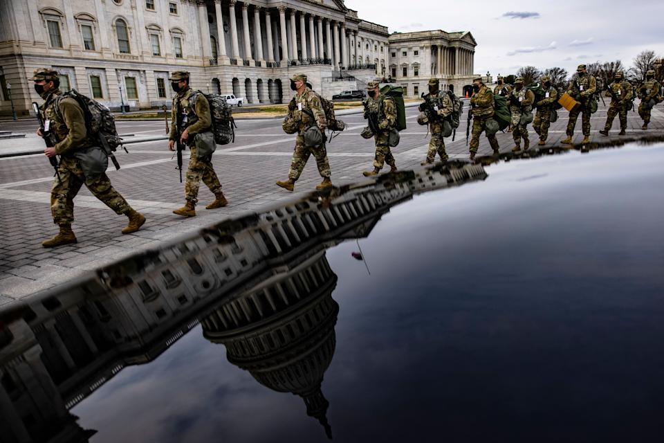 Virginia National Guard troops march across the east front of the U.S. Capitol on their way to their guard posts on Jan. 16 in Washington, DC. After the Jan. 6 riots at the U.S. Capitol, the FBI has warned of additional threats in the nation's capital and in all 50 states. (Photo: Samuel Corum via Getty Images)