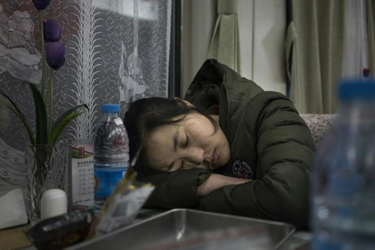 People sleep in the restaurant car during the train journey from Beijing to Chengdu, as travellers head home from the capital ahead of the Lunar New Year