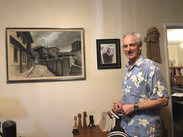 William Yankes stands beside the painting created by his late father.