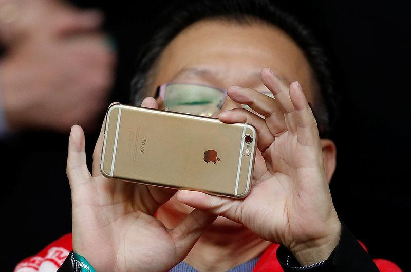 FILE PHOTO: A man uses an Apple iPhone to take photographs before the Liverpool versus Tottenham Hotspur soccer match at Anfield in Liverpool northern England.