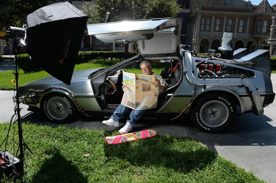 """Bob Gale, co-writer and co-producer of the """"Back to the Future movies,"""" looks over a copy of USA TODAY while sitting in a restored DeLorean time machine owned by screenwriter Terry Matalas in Courthouse Square at Universal Studios, Los Angeles, in 2015."""