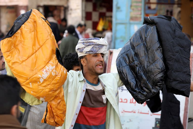 A vendor sells second hand clothes at a market in Sanaa