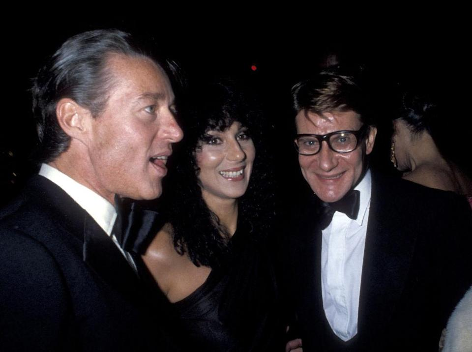NEW YORK CITY - SEPTEMBER 20: Fashion designer Halston, singer Cher and fashion designer Yves Saint Laurent attend Yves Saint Laurent's 'Opium' Perfume Launch Party on September 20, 1978 aboard The Peking, South Street Seaport in New York City. (Photo by Ron Galella/Ron Galella Collection via Getty Images)