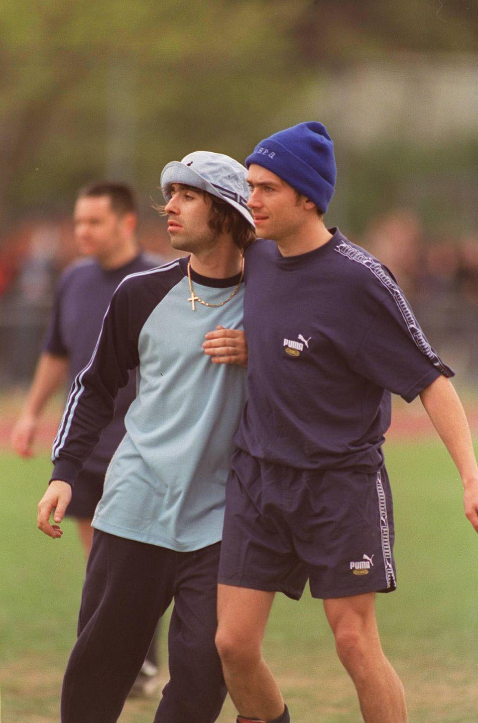 <p>Liam Gallagher of Oasis and Damon Albarn, lead singer of Blur, play in a charity soccer tournament in 1996,</p>