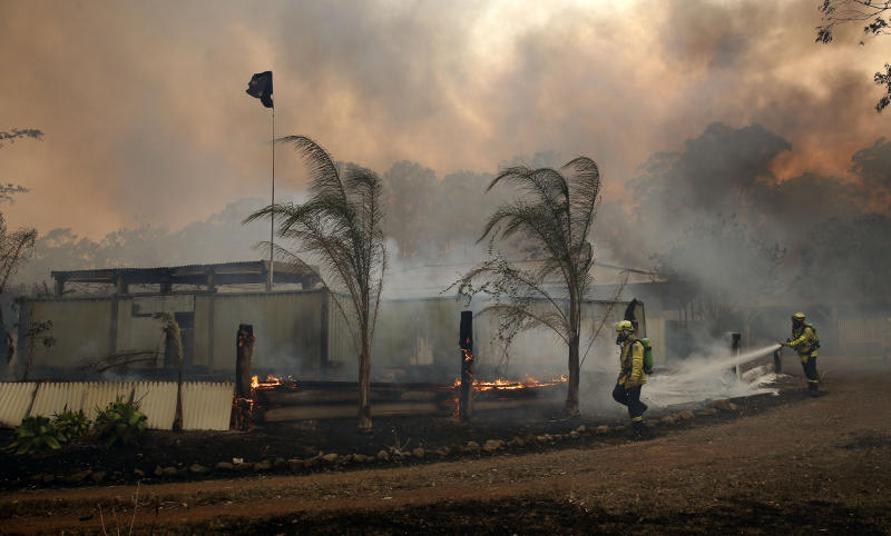 Two firefighters try to save a house south of Taree on Tuesday as smoke fills the surrounding area.
