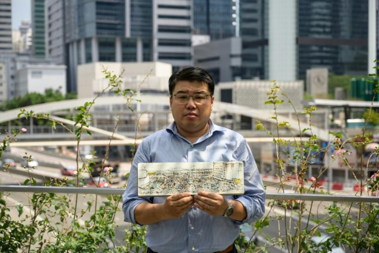 Artist Alvin Wong, founder of Hong Kong's Urban Sketchers group, poses with a drawing that he produced during the 2014 Umbrella Movement pro-democracy protests in the Admiralty district of Hong Kong
