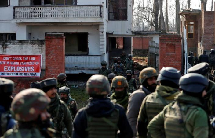 Indian army soldiers stand outside a house after a gun battle with suspected militants in Hokarsar