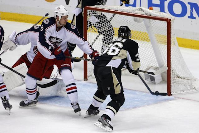 Pittsburgh Penguins' Jussi Jokinen (36) gets his stick on the loose puck and pokes it in for a goal past Columbus Blue Jackets goalie Sergei Bobrovsky and Nikita Nikitin (6) in the third period of Game 5 of a first-round NHL playoff hockey series in Pittsburgh, Saturday, April 26, 2014. The Penguins won 3-1. (AP Photo/Gene J. Puskar)
